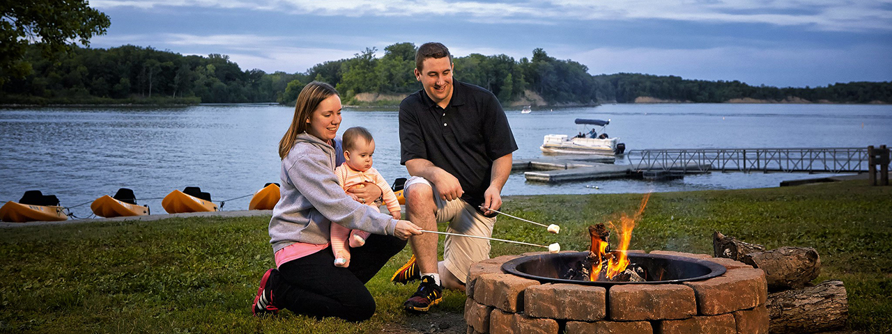 Family roasting marshmallows on a campfire by a lake